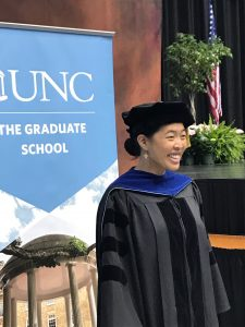 A graduate student in academic regalia smiles while standing in front of a banner that reads UNC The Graduate School